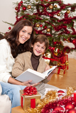 Fotografie Young mother with son reading book on Christmas