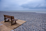 Fotografie Wooden bench at a pebbles beach