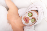 Body care series - Young lady with facial mask and cucumber