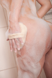 Body care: Woman in shower with washcloth and foam