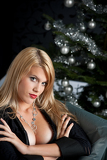 Portrait of blond sexy woman in black dress on Christmas