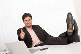 Fotografia Successful businessman gesturing at office, thumbs-up