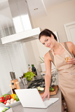 Cheerful woman with laptop in the kitchen