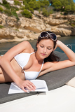 Fotografia Attractive woman sunbathing on luxury boat