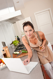 Woman with glass of white wine and laptop in the kitchen