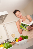 Young woman reading cookbook in the kitchen