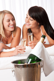 Fotografie Two women toasting with champagne in bedroom
