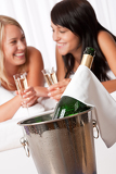 Two smiling women drinking champagne in luxury hotel room