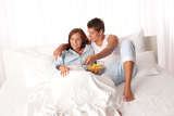 Fotografia Young man and woman lying down in white bed