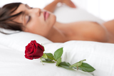 Woman lying in white bed, focus on rose