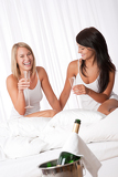 Two happy women having fun with champagne