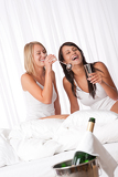 Two women having fun in luxury hotel room