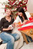 Two young woman wrapping Christmas present