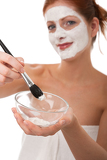 Body care series - Young woman applying white facial mask