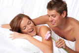 Photo Happy man and woman lying down in bed together