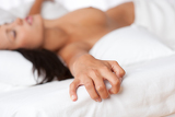 Fotografie Naked woman lying in bed, focus on hand
