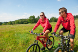Fényképek Young couple riding mountain bike in spring meadow