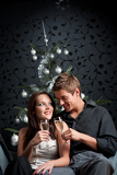 Fotografie Young extravagant man and woman with champagne on Christmas