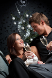 Young extravagant man and woman with champagne on Christmas