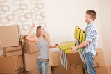 Fotografia Moving house: Man and woman with box and chair
