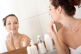 Body care series - Young woman cleaning her face in the bathroom