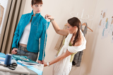Fotografia Female fashion designer measuring jacket on model