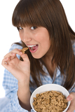 Female teenager eat healthy cereal for breakfast