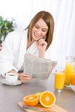 Photo Breakfast - Smiling woman reading newspaper in kitchen