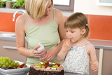 Mother and child with chocolate cake in kitchen