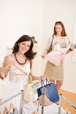 Fashion shopping - Two Happy woman choose sale clothes
