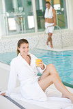 Fotografia Young woman in bathrobe relax at swimming pool