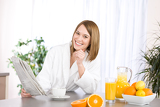 Fotografie Breakfast - Smiling woman reading newspaper in kitchen