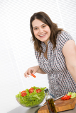 Cook - Plus size happy woman preparing salad in kitchen
