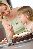 Fotografie Mother and child tasting chocolate cake in kitchen