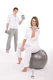 Fitness - Young couple exercise with weights and ball