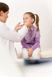 Female doctor examining child with sore throat