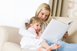Mother with surprised little girl read book