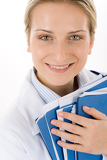 Fotografie Young female doctor with medical files on white