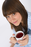 Female teenager with cup of tea for breakfast