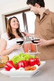 Happy couple in kitchen, focus on vegetable