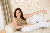 Smiling woman relax on sofa in lounge