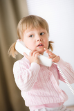 Little girl holding telephone receiver calling