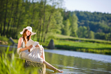 Fényképek Long red hair romantic woman relax by lake with book