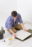 Fotografie Home improvement - handyman laying tile