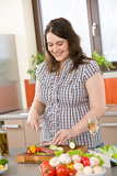 Cook - plus size woman cutting salami and vegetable