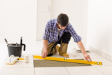 Fotografie Home tile improvement - handyman with level