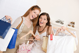 Fotografie Fashion shopping -  Two happy young woman choose clothes