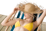 Beach - woman with straw hat in yellow bikini sunbath