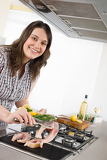 Cook - plus size woman grill fish in kitchen