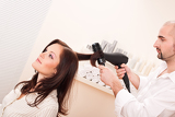 Fotografie Professional hairdresser with hair dryer at salon with customer